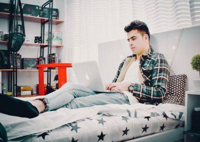 fiú ül az ágyán, laptoppal az ölében