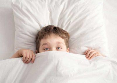 kisfiú meglepődve néz ki a takaró alól