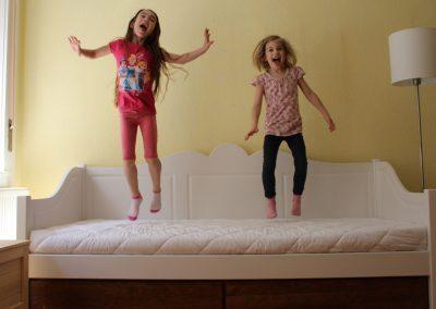 két kislány vidáman ugrál egy fehér rusztikus kanapéágyon