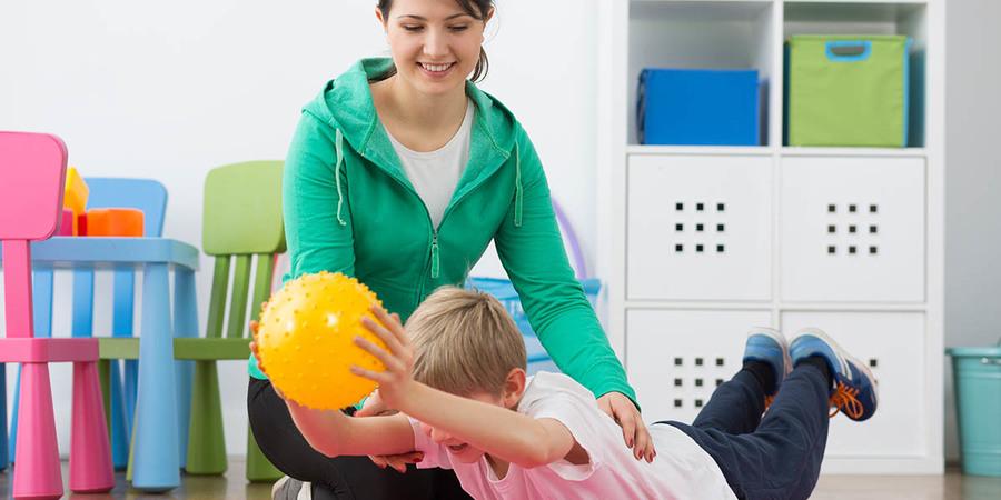 egy kisfiú egy labdával tornázik egy gyógytornász segítségével